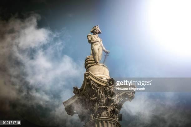 nelson's column in the clouds - estátua imagens e fotografias de stock