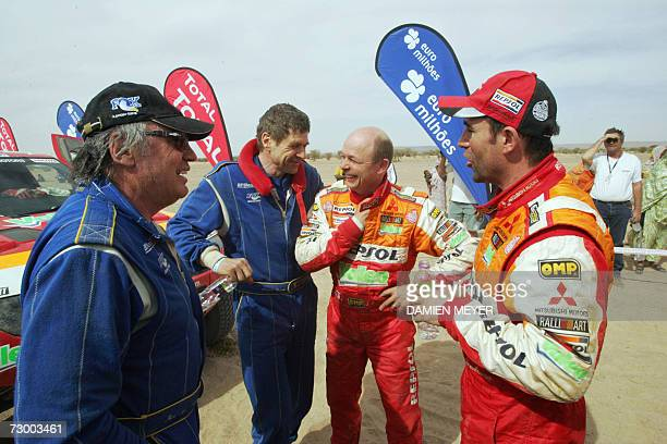France's driver JeanLouis Schlesser his codriver Arnaud Debron codriver JeanPaul Cottret and his driver Stephane Peterhansel chat at the finish of...