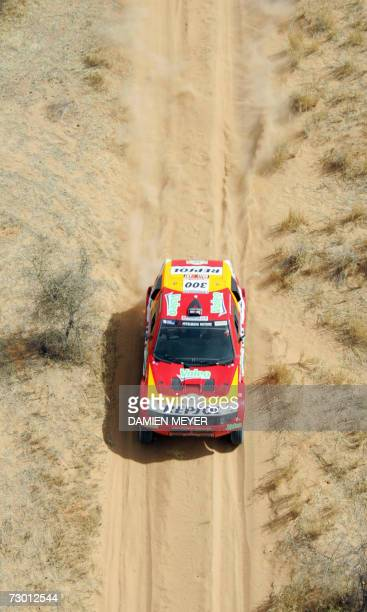 France's Luc Alphand jumps with his Mitsubishi during the tenth stage of the 29th Dakar NemaNema 16 January 2007 France's Stephane Peterhansel leads...