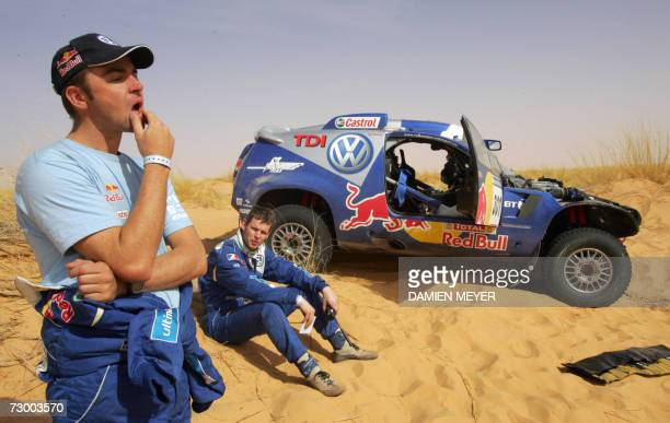 South Africa's Giniel De Villiers looks dejected with codriver Dirk Von Zitzewitz after their Volkswagen's got fire during the ninth stage of the...
