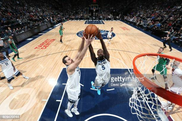 Nemanja Bjelica and Gorgui Dieng of the Minnesota Timberwolves go for a rebound against the Boston Celtics on March 8 2018 at Target Center in...