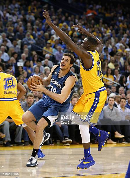 Nemanja Bjelica of the Minnesota Timberwolves drives on Draymond Green of the Golden State Warriors at ORACLE Arena on April 5 2016 in Oakland...