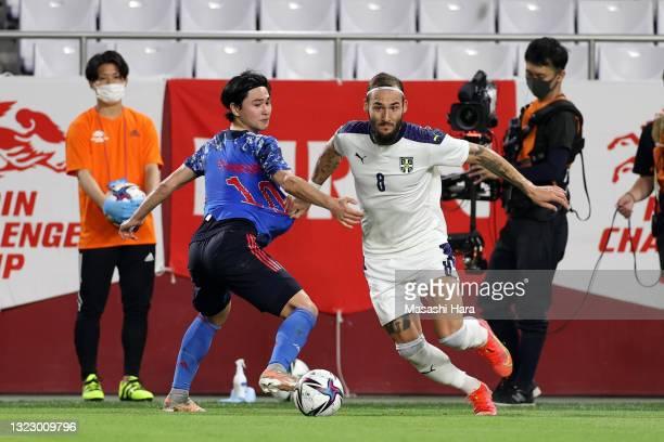 Nemanja Gudelj of Serbia goes past Takumi Minamino of Japan during the international friendly match between Japan and Serbia at Noevir Stadium Kobe...