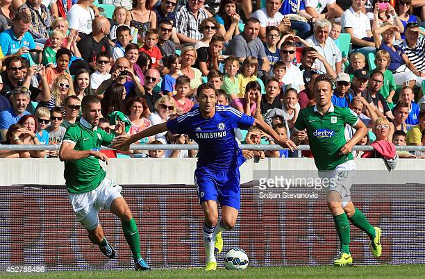 Nemanja Matic of Chelsea in action against Kenan Bajric and Antonio Mlinar Delamea of FC Olimpija Ljubljana during the Pre Season Friendly match...