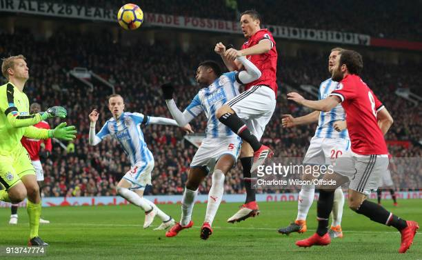 Nemanja Matic of Man Utd wins a header over Terence Kongolo of Huddersfield but the header goes wide during the Premier League match between...