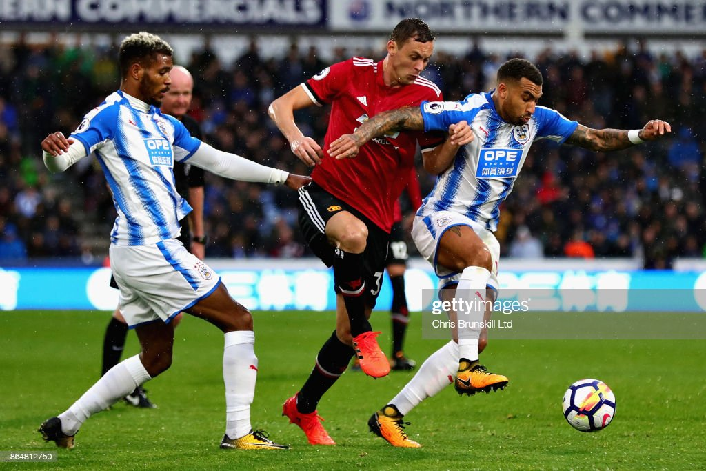Nemanja Matic of Manchester United battles with Martin Cranie Danny Williams, both of Huddersfield Town during the Premier League match between Huddersfield Town and Manchester United at John Smith's Stadium on October 21, 2017 in Huddersfield, England.