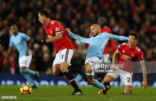 Nemanja Matic of Manchester United is tackled by David Silva of Manchester City during the Premier League match between Manchester United and...