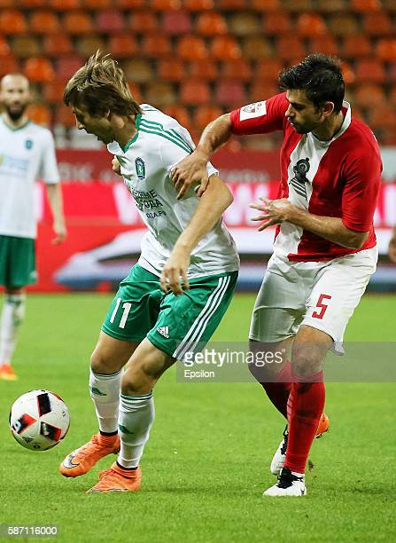 Nemanja Pejchinovich of FC Lokomotiv Moscow challenged by Oleksandr Kasyan of FC Tom Tomsk during the Russian Premier League match between FC...