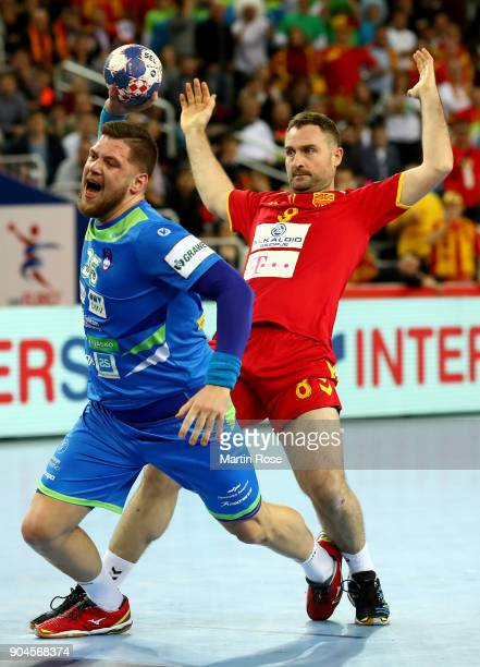 Nemanja Pribak of Macedonia challenges Matic Suholeznik of Slovenia during the Men's Handball European Championship Group C match between Macedonia...