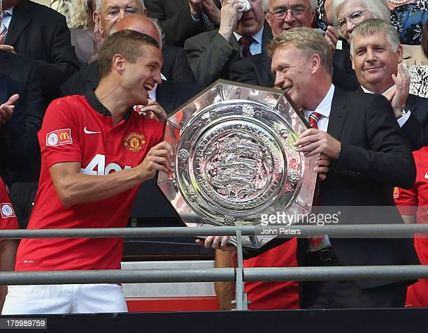 Nemanja Vidic and Manager David Moyes of Manchester United pose with the FA Community Shield trophy after the FA Community Shield match between...