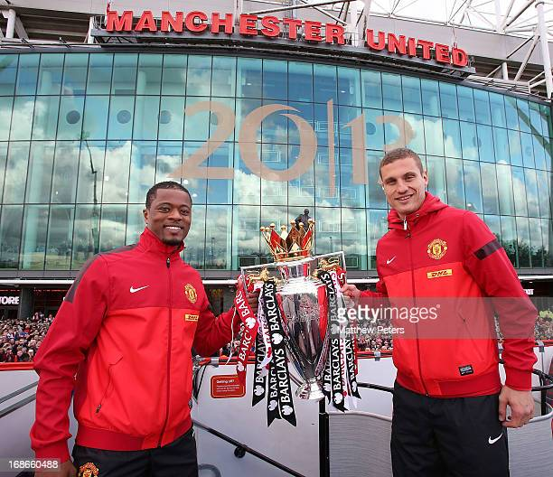 Nemanja Vidic and Patrice Evra of Manchester United pose with the Premier League trophy at the start of the Premier League trophy winners parade on...