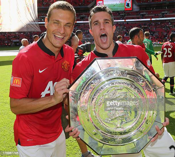 Nemanja Vidic and Robin van Persie of Manchester United pose with the FA Community Shield trophy after the FA Community Shield match between...