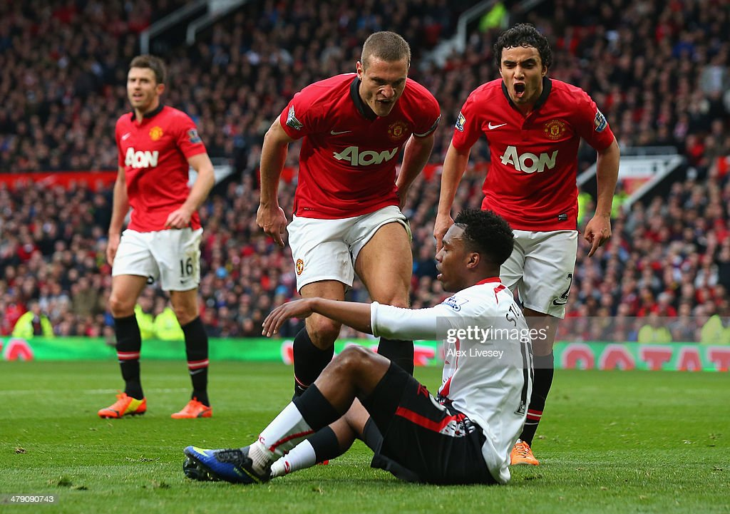Nemanja Vidic of Manchester United and Rafael (R) react to Daniel Sturridge of Liverpool after the award of the second penalty kick during the Barclays Premier League match between Manchester United and Liverpool at Old Trafford on March 16, 2014 in Manchester, England.