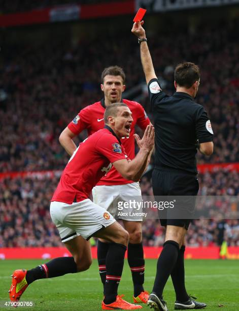 Nemanja Vidic of Manchester United is shown a red card by Referee Mark Clattenburg during the Barclays Premier League match between Manchester United...