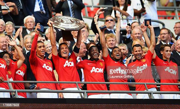 Nemanja Vidic of Manchester United lifts the trophy and celebrates with team mates after victory in the FA Community Shield match between Manchester...