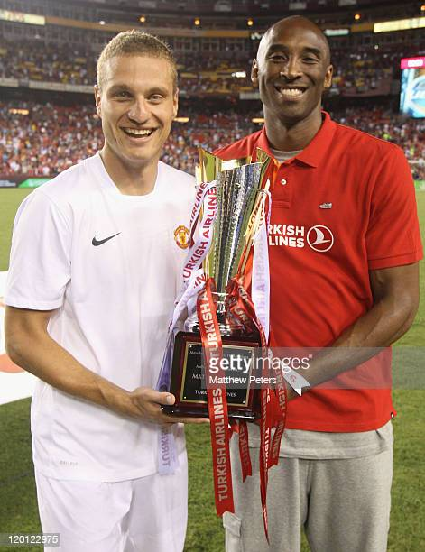 Nemanja Vidic of Manchester United poses with basketball star Kobe Bryant and the Turkish Airlines trophy after the preseason friendly match between...