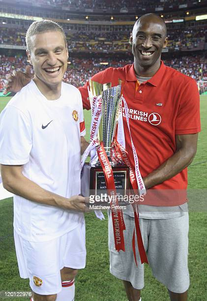 Nemanja Vidic of Manchester United poses with basketball star Kobe Bryant and the Turkish Airlines trophy after the pre-season friendly match between...