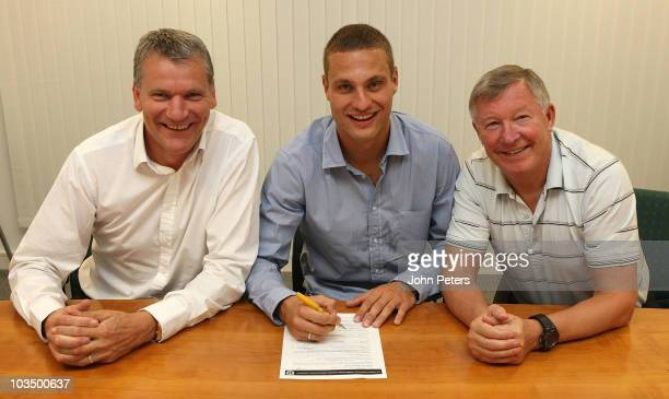 Nemanja Vidic of Manchester United poses with Chief Executive David Gill and Sir Alex Ferguson after signing an extension to his contract at...
