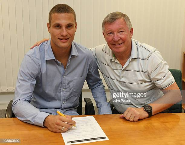 Nemanja Vidic of Manchester United poses with Sir Alex Ferguson after signing an extension to his contract at Carrington Training Ground on August...