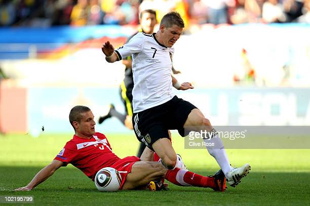Nemanja Vidic of Serbia tackles Bastian Schweinsteiger of Germany during the 2010 FIFA World Cup South Africa Group D match between Germany and...