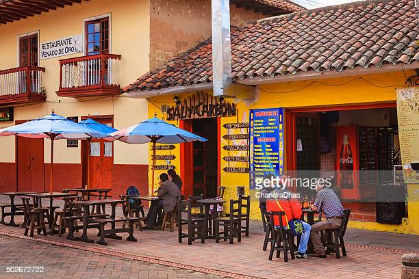 Nemocón, Colombia: people at roadside restaurant; colonial architecture