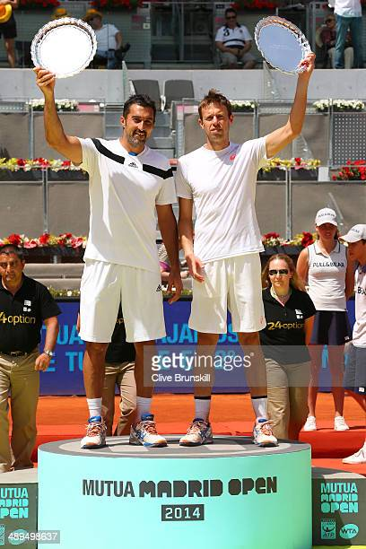 Nenad Zimonjic of Serbia and Daniel Nestor of Canada hold their trophies aloft after their straight sets victory against Bob Bryan and Mike Bryan of...