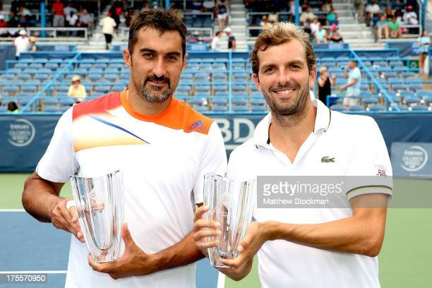 Nenad Zimonjic of Serbia and Julien Benneteau of France pose for photographers after defeating Mardy Fish and Radek Stepanek of Czech Republic during...