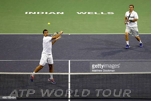 Nenad Zimonjic of Serbia and Marcin Matkowski of Poland play Dominic Inglot of Great Britain and Florin Mergea of Romania during day ten of the BNP...