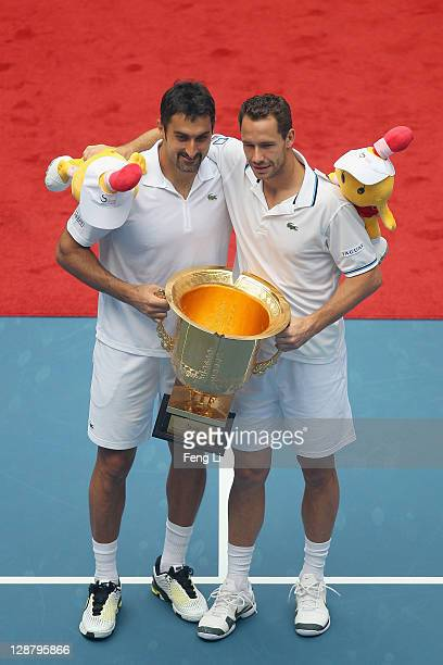 Nenad Zimonjic of Serbia and Michael Llodra of France pose for photographers after winning the men's doubles final of the China Open at the National...