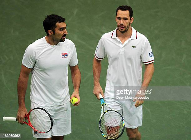 Nenad Zimonjic of Serbia and Michael Llordra of France speak during their Doubles match against Alex Bogomolov of Russia dn Dick Norman of Belgium in...
