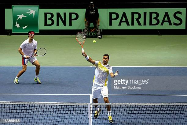 Nenad Zimonjic of Serbia returns a shot to Mike and Bob Bryan while playing with and Ilija Bozoljac of Serbia in the third rubber during the Davis...