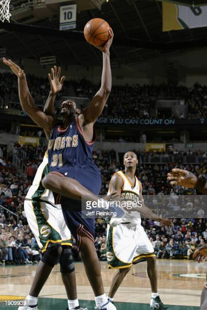 Nene Hilario of the Denver Nuggets drives to the basket during the NBA game against the Seattle Sonics at Key Arena on March 21 2003 in Seattle...