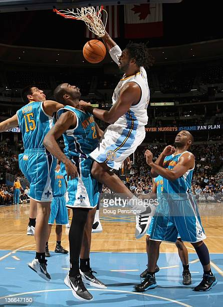 Nene Hilario of the Denver Nuggets dunks the ball on DaJuan Summers of the New Orleans Hornets at the Pepsi Center on January 9 2012 in Denver...