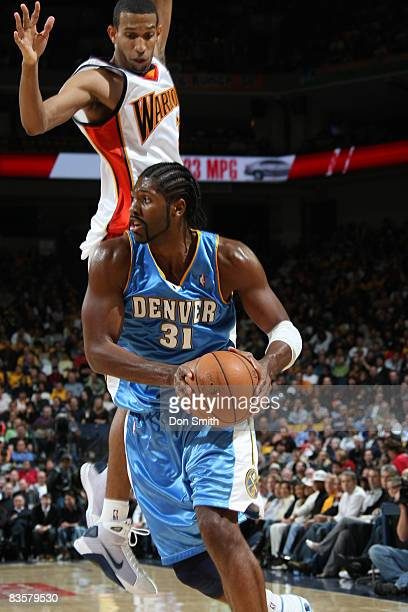 Nene Hilario of the Denver Nuggets makes a pump fake against Brandan Wright of the Golden State Warriors on November 5 2008 at Oracle Arena in...