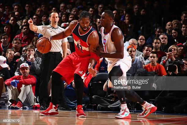 Nene Hilario of the Washington Wizards handles the basketball against Samuel Dalembert of the New York Knicks at Madison Square Garden on December 25...