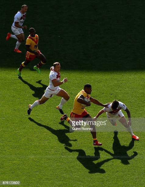 Nene MacDonald of Papua New Guinea breaks through the English defence during the 2017 Rugby League World Cup Quarter Final match between England and...