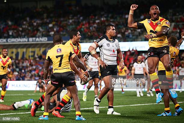 Nene Macdonald of Papua New Guinea celebrates with team mates after scoring a try during the International Rugby League Test match between Fiji and...