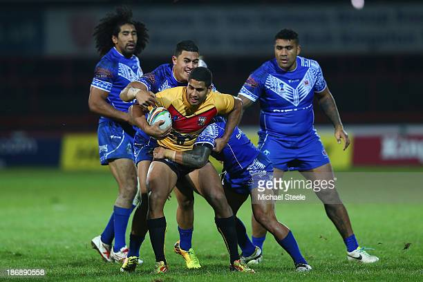 Nene McDonald of Papua New Guinea is tackled by Tim Lafai of Samoa during the Rugby League World Cup Group B match between Papua New Guinea and Samoa...