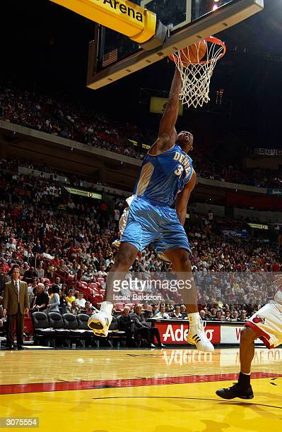 Nene of the Denver Nuggets dunks the ball during the game against the Miami Heat at American Airlines Arena on February 21 2004 in Miami Florida The...