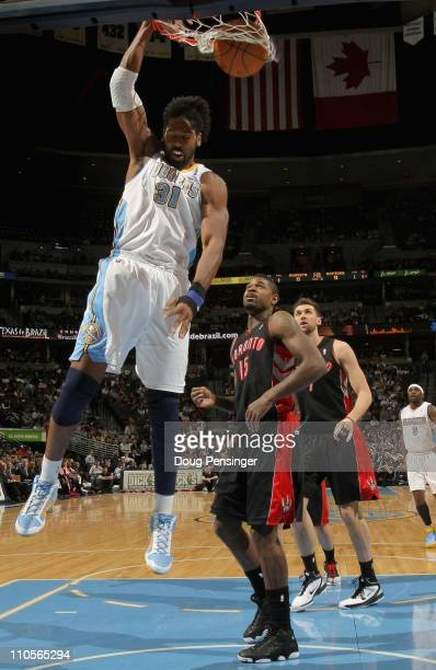 Nene of the Denver Nuggets dunks the ball in front of Amir Johnson of the Toronto Raptors at the Pepsi Center on March 21 2011 in Denver Colorado...