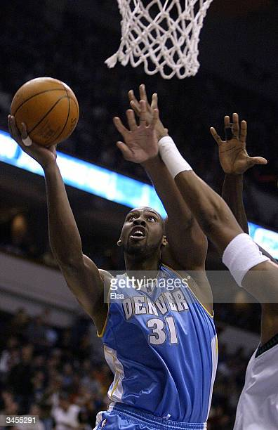 Nene of the Denver Nuggets goes up for a shot as Ervin Johnson of the Minnesota Timberwolves defends on April 21 2004 at the Target Center in...