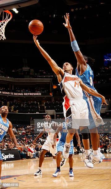 Nene of the Denver Nuggets guards against DJ Augustin of the Charlotte Bobcats on November 11 2008 at the Time Warner Cable Arena in Charlotte North...