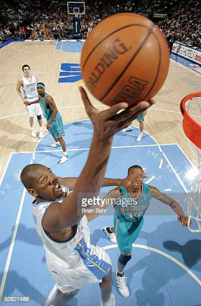 Nene of the Denver Nuggets takes the ball to the net against David West of the New Orleans Hornets in the second half on April 13 2005 at the Pepsi...