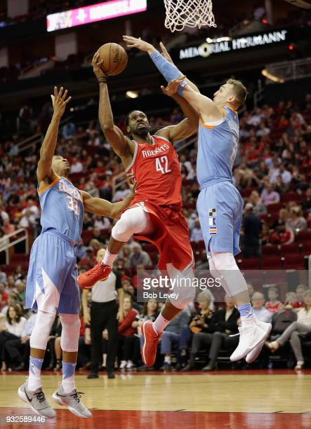 Nene of the Houston Rockets drives to the basket between Sam Dekker of the LA Clippers and Wesley Johnson at Toyota Center on March 15 2018 in...