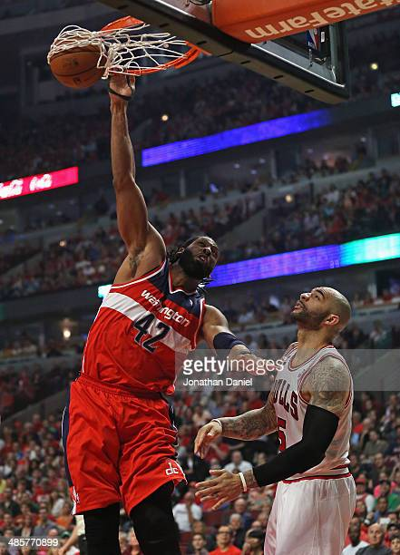 Nene of the Washington Wizards dunks over Carlos Boozer of the Chicago Bulls in Game One of the Eastern Conference Quarterfinals during the 2014 NBA...