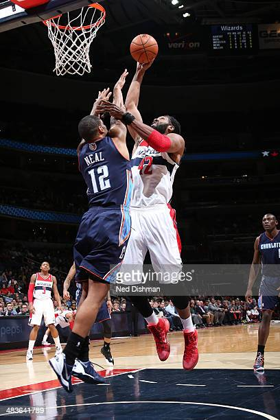 Nene of the Washington Wizards shoots against Gary Neal of the Charlotte Bobcats during the game at the Verizon Center on April 9 2014 in Washington...