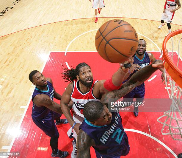Nene of the Washington Wizards shoots against Marvin Williams of the Charlotte Hornets during a game at the Verizon Center on March 27 2015 in...