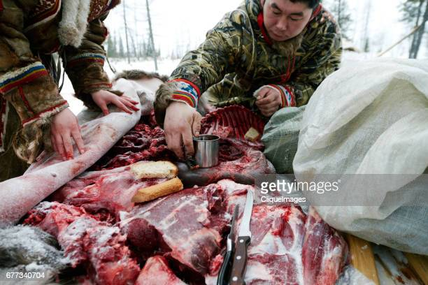 nenets people eating reindeer meat - cliqueimages stock pictures, royalty-free photos & images