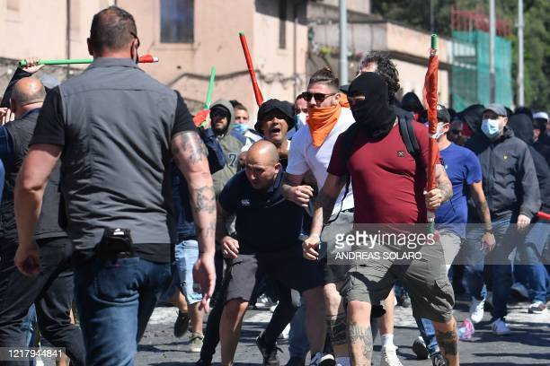 Neo-fascist groups, extremists and ultras from Italy's football clubs clash with plainclothes policemen as they demonstrate over the government's...