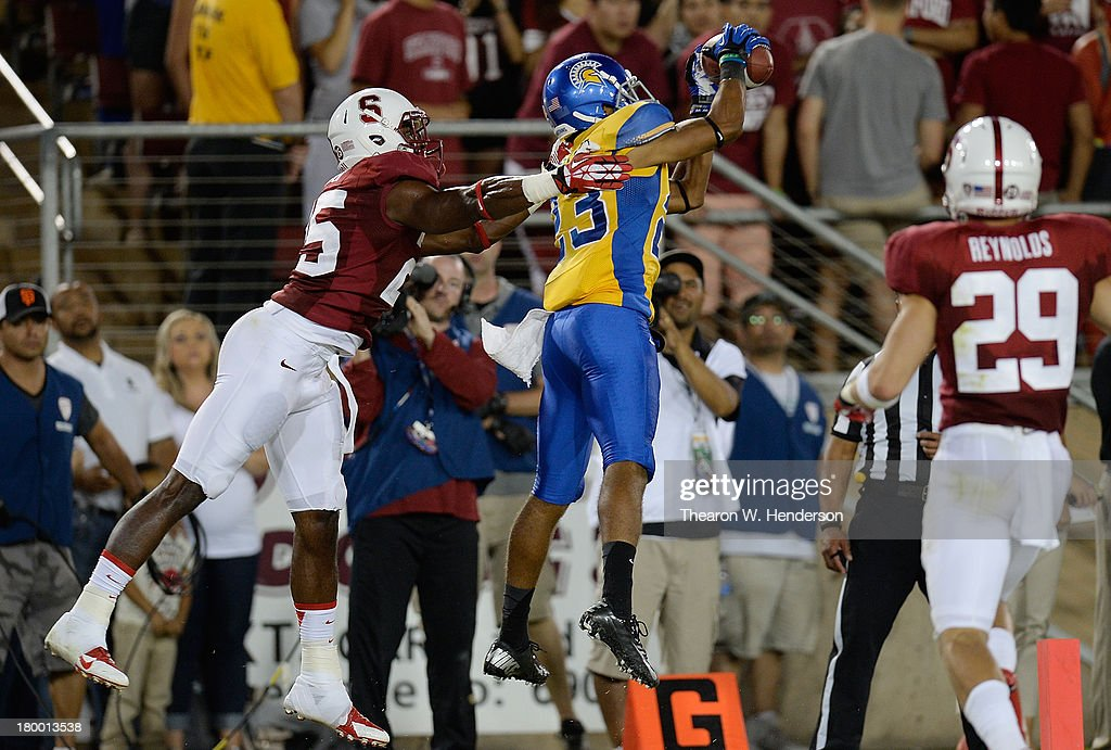 Neol Grigsby #23 of the San Jose State Spartans catches a thirteen yard touchdown pass in front of Alex Carter #25 of the Stanford Cardinal during the third quarter at Stanford Stadium on September 7, 2013 in Palo Alto, California. The Cardinals won the game 34-13.